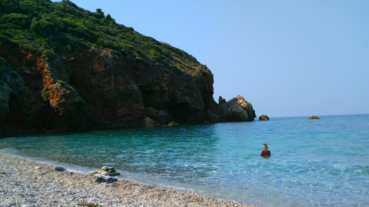 The pebbly beach of Lyri in Southern Pelion, Central Greece including the clear blue-green water.
