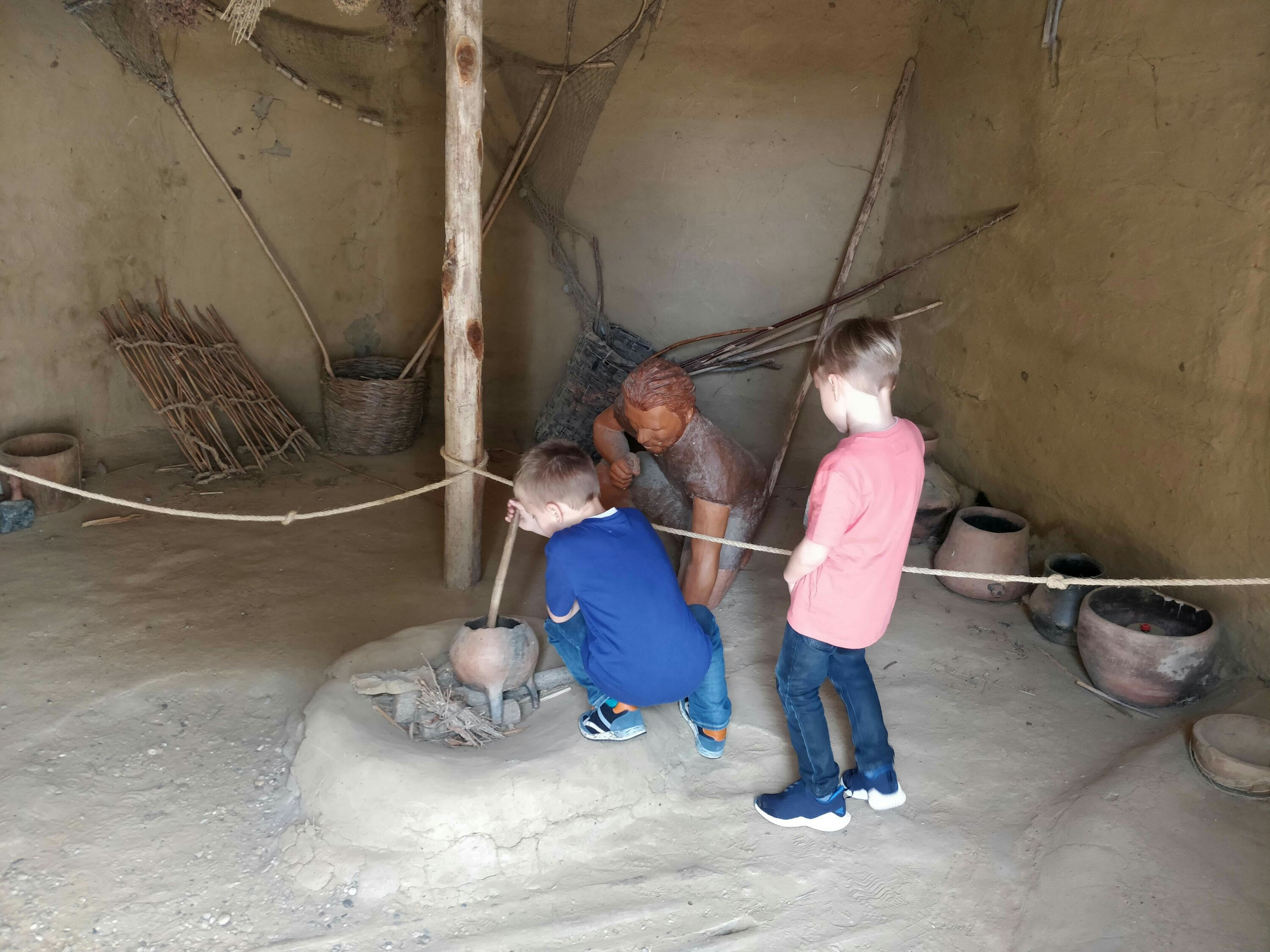 Photo of two children with a statue of a prehistoric man in a reproduction of a neolithic cave pretending to cook